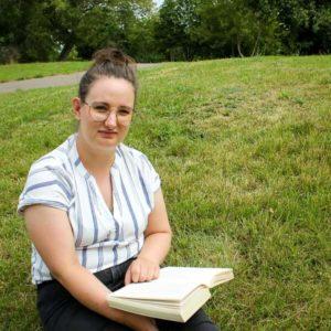 Fridaygirl sitzt auf der Wiese und liest ein Liebesroman